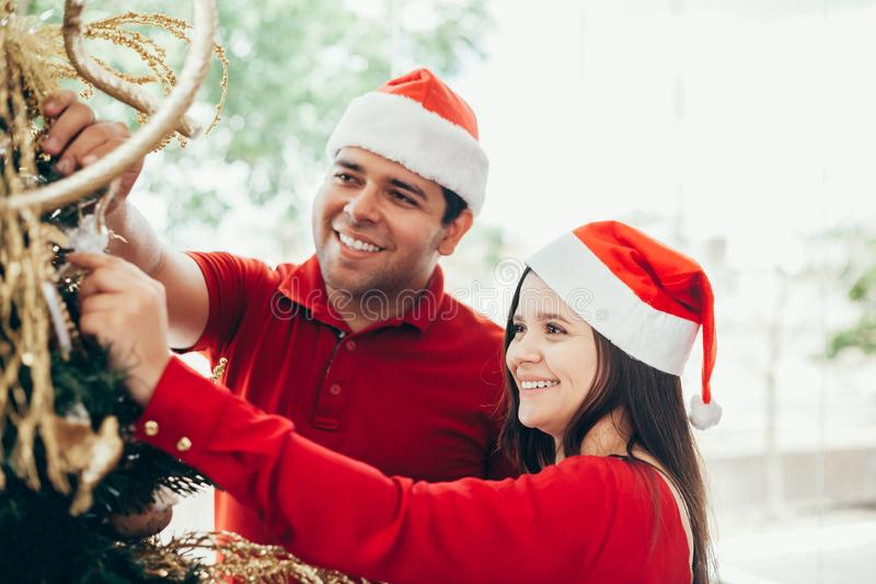 Young couple decorating a Christmas tree stock photos
