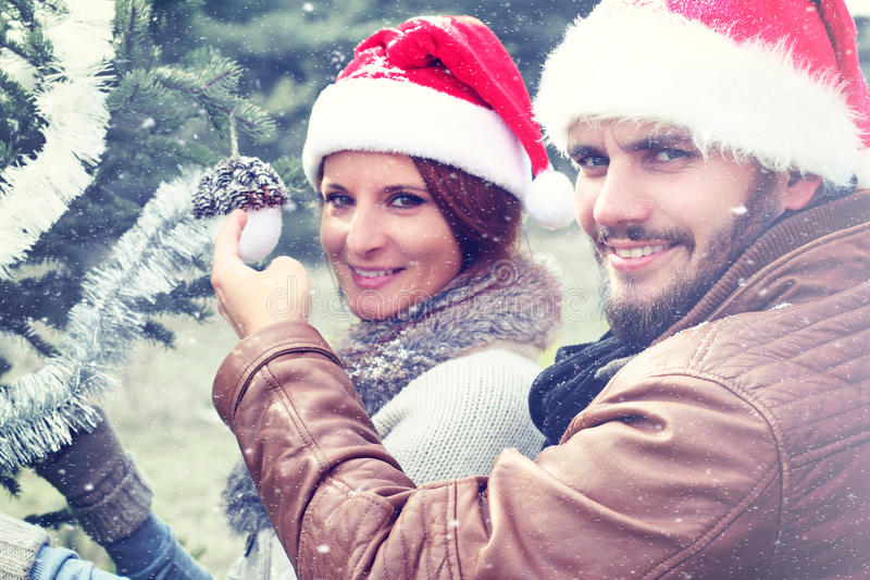 Young Couple Decorating Christmas Tree outdoor. Young Man and Woman together Celebrating Christmas outdoor stock image