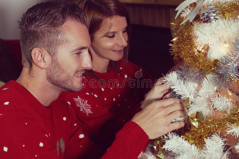 Young couple decorating a Christmas tree. Young couple wearing a red sweater decorating a Christmas tree stock image