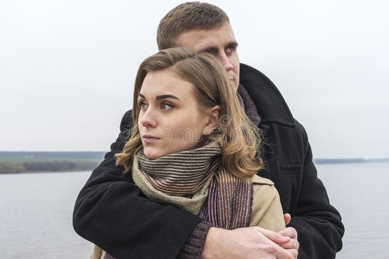 Young couple deeply in love in a close embrace. As they stand close together in warm winter outfits outdoors on a cold misty day stock images