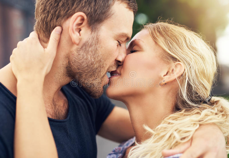 Young couple deeply in love. Sharing a romantic kiss, closeup profile view of their faces royalty free stock photography