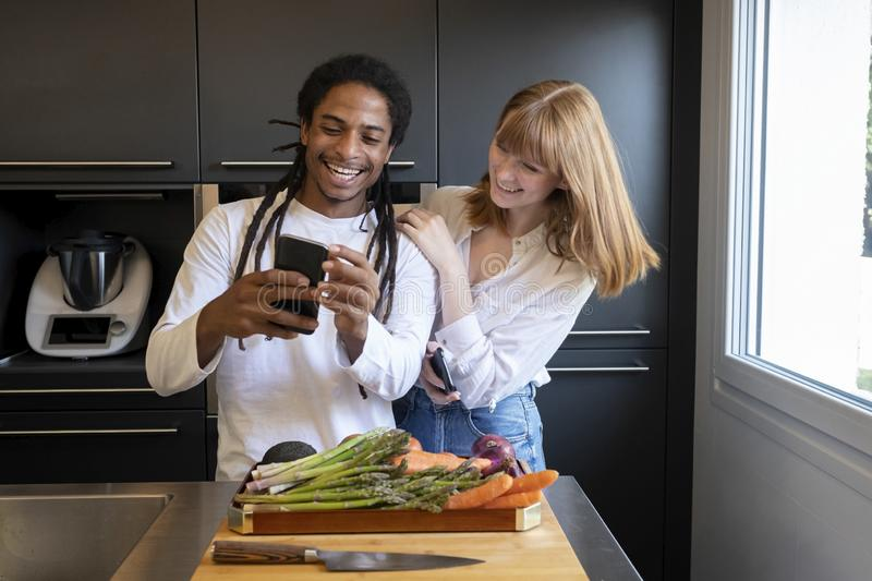 Young couple of different ethnic groups with mobile phone in a kitchen with vegetable board. concept of healthy living.  stock image
