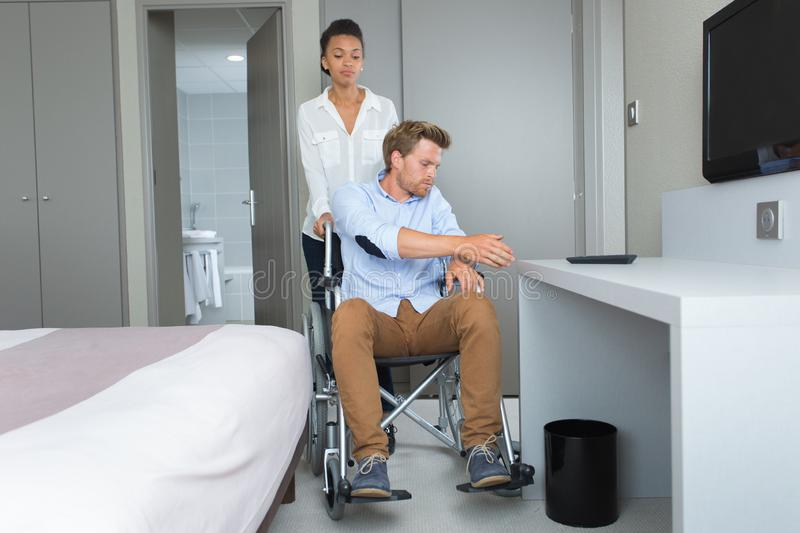 Young couple with disabled boyfriend in hotel room stock photo