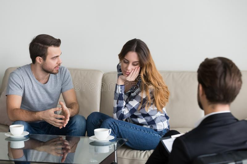Young couple discuss relationships problems at counselor. Millennial couple discuss family problems sitting on couch at counselor or psychologist, male stock image