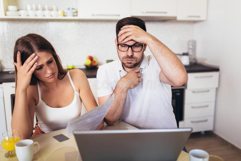 Couple discussing about home budget in the kitchen royalty free stock image