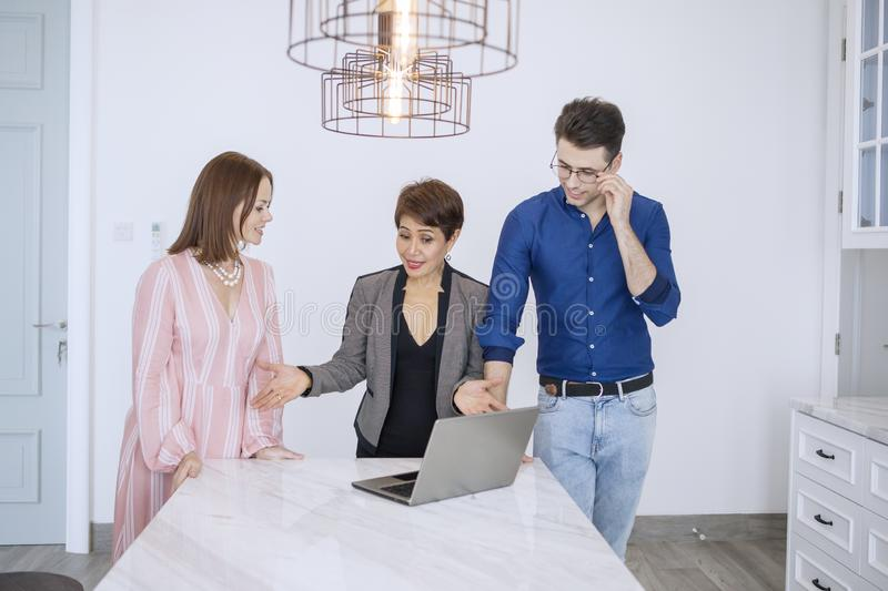 Young couple discussing with a real estate agent. Young couple discussing house for sale with a real estate agent while standing together at indoor royalty free stock photos