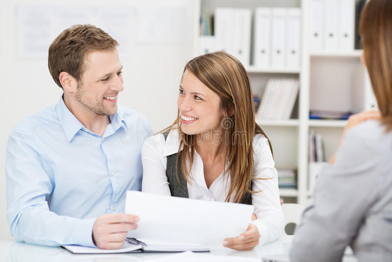Young couple discussing an investment presentation. Young couple sitting at a desk in the office of their agent or adviser discussing an investment presentation stock photos
