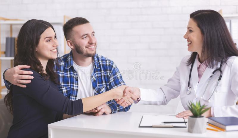 Young couple at doctor`s office during visit. Grateful women shaking the doctor`s hand, panorama with free space royalty free stock image