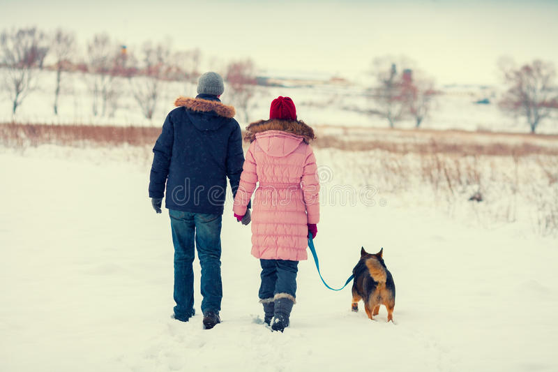 Young couple with dog walking in the snowy field. Young happy couple with dog walking in the snowy field back to camera royalty free stock image