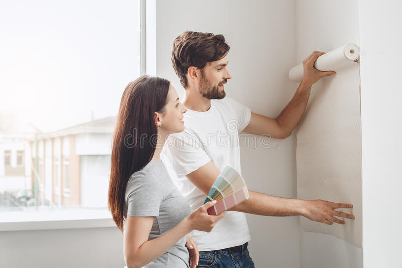 Young couple doing apartment repair together themselves. Young men and women doing apartment repair together wallpapering royalty free stock photo