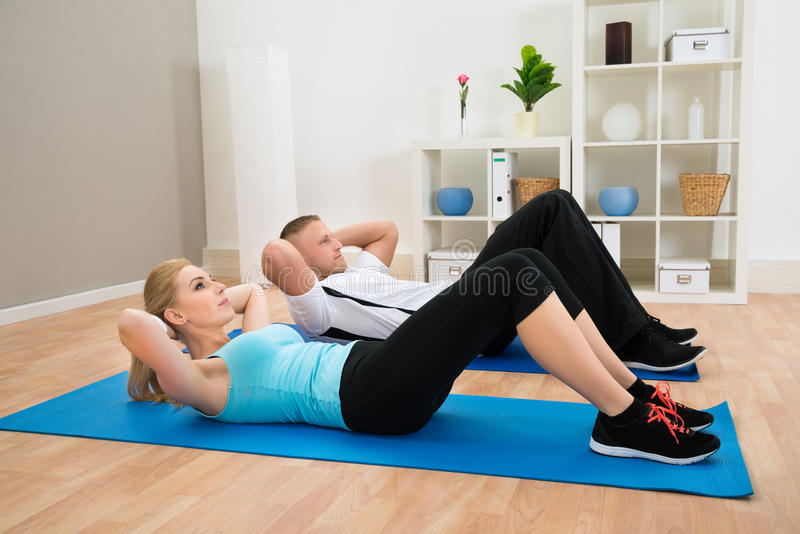 Young Couple Doing Crunches stock images