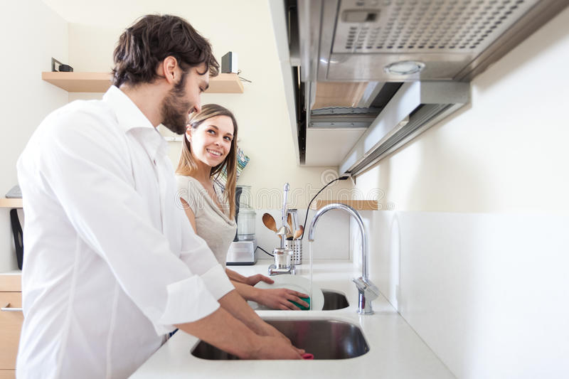Young couple doing dishes. In the kitchen royalty free stock images