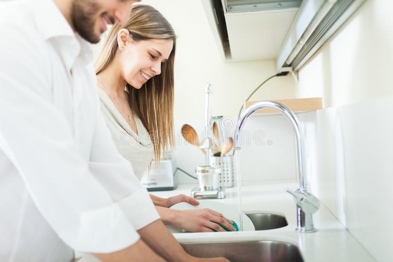 Young couple doing dishes. In the kitchen royalty free stock image