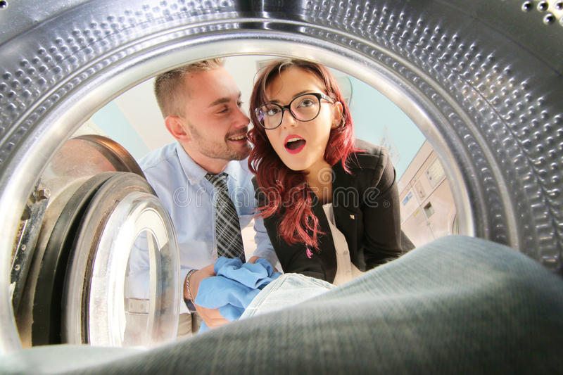 Young couple doing laundry seen from washing machine royalty free stock images