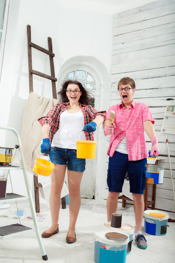 Young couple doing repair at home. Funny and crazy smiling young couple with paint cans in their hands and paint brush doing repair at home. White background royalty free stock photography