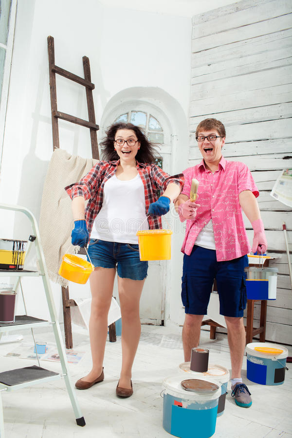 Young couple doing repair at home. Funny and crazy smiling young couple with paint cans in their hands and paint brush doing repair at home. White background stock photos