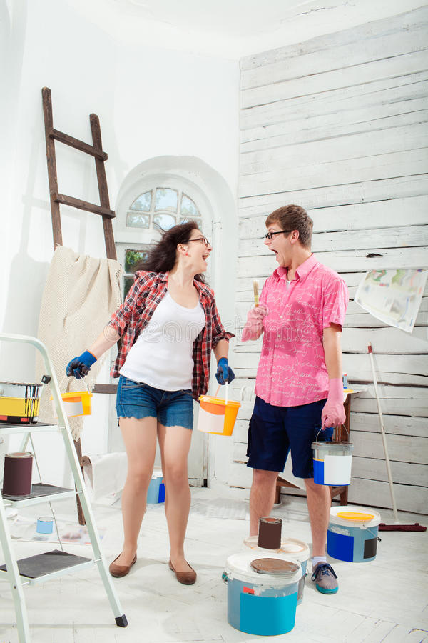 Young couple doing repair at home. Funny and crazy terrified young couple with paint cans in their hands and paint brush doing repair at home. White home stock image