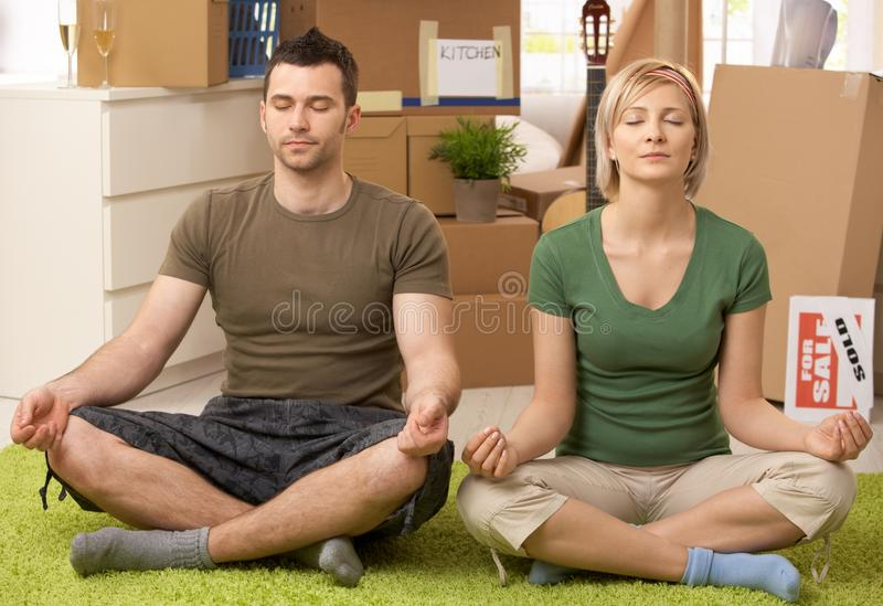 Young couple doing yoga at new house. Young couple doing yoga meditation in new house after moving, sitting in middle of boxes stock photos