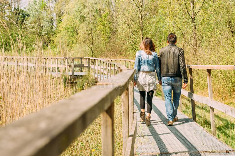 Young couple, dressed in modern casual way, walking on wooden pier during sunny day in the woods, immersed in nature. Couple of lovers walking in wooden pier royalty free stock photos