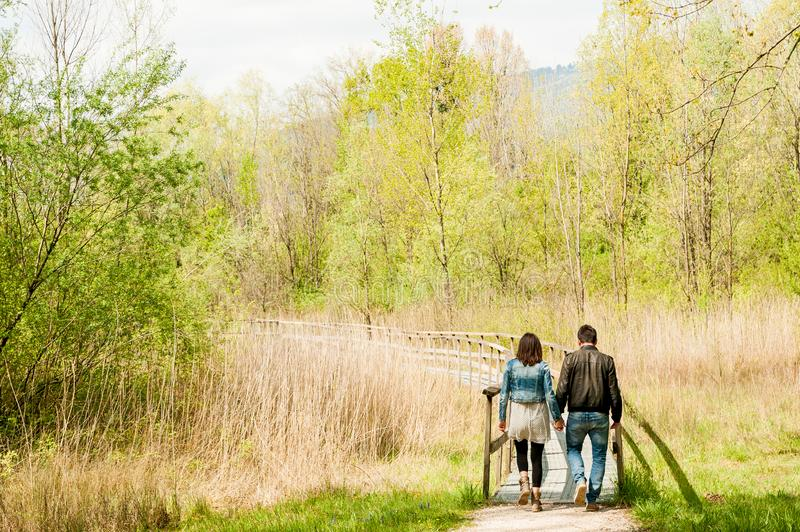 Young couple, dressed in modern casual way, walking on wooden pier during sunny day in the woods, immersed in nature. Couple of lovers walking in wooden pier stock photo