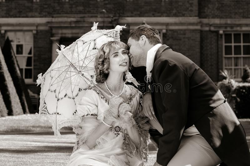 Young couple dressed in vintage costume relaxing with man on one knee, kissing on lawn in front of stately home stock photo