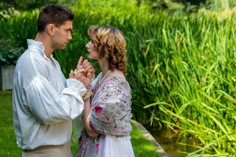 Young handsome couple dressed in vintage costume standing on embankment by river, holding hands, looking at each other stock photography