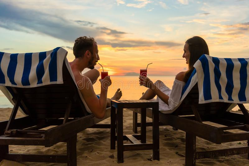 Young couple drinking cocktails on a beach at sunset during vacation stock image