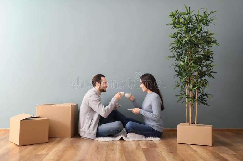 Young couple drinking coffee near boxes indoors. Moving into new house royalty free stock photo