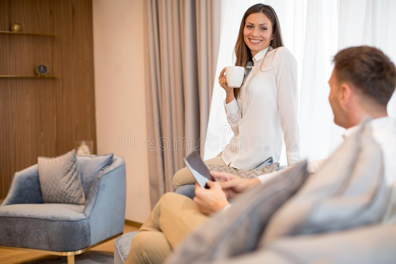 Young couple drinking coffee and using digital tablet in the contemporary apartment. Young couple drinking coffee and using digital tablet in the luxury royalty free stock photos