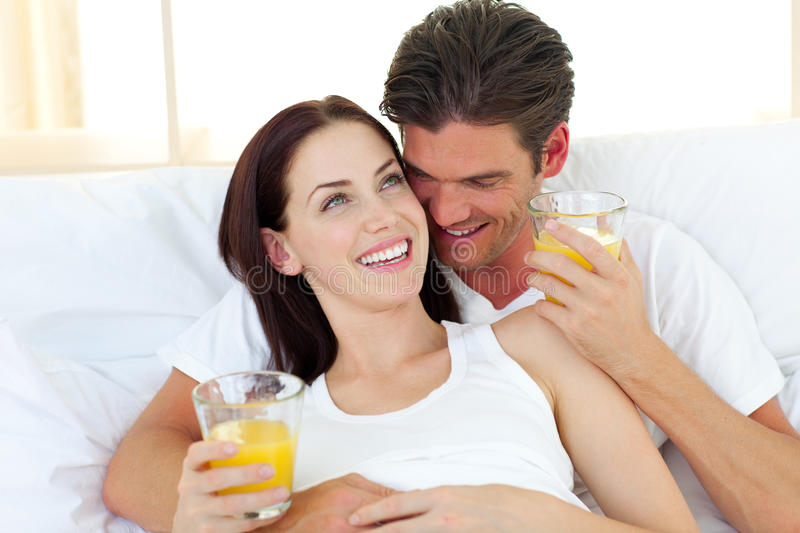 Young couple drinking orange juice on their bed stock photography