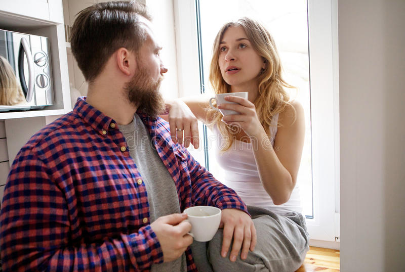 Young couple is drinking tea and coffee at home stock photo