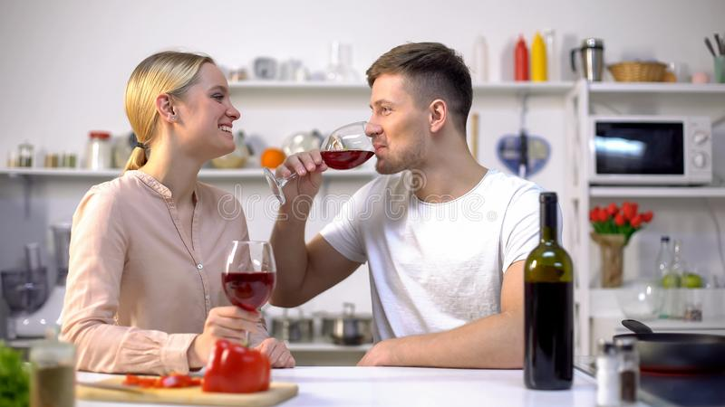 Young couple drinking wine in kitchen, chatting and relaxing together, romance royalty free stock photos