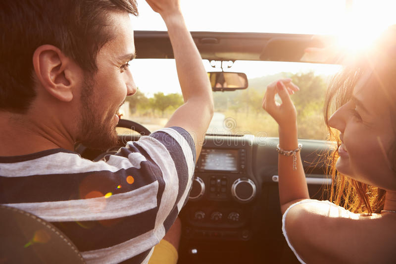 Download Young Couple Driving Along Country Road In Open Top Car Stock Photo - Image of soft, male: 52857090