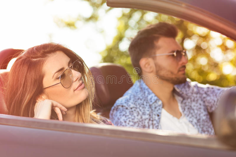 Young Couple Driving Along Country Road In Open Top Car royalty free stock images