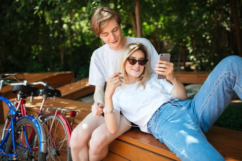 Young couple in earphones listening music while spending time in park with two bicycles nearby. Boy sitting on bench in stock images