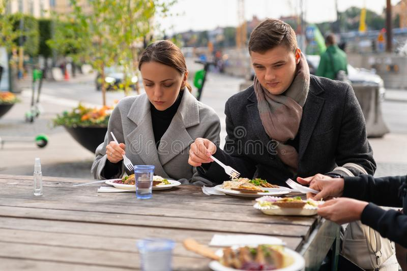 Young couple eating with friends or family stock photography