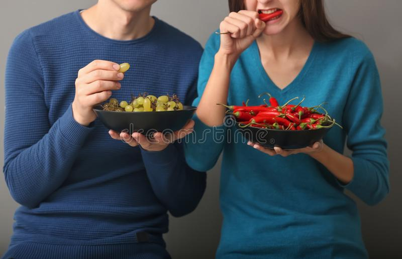 Young couple eating grapes and chili on grey background stock image