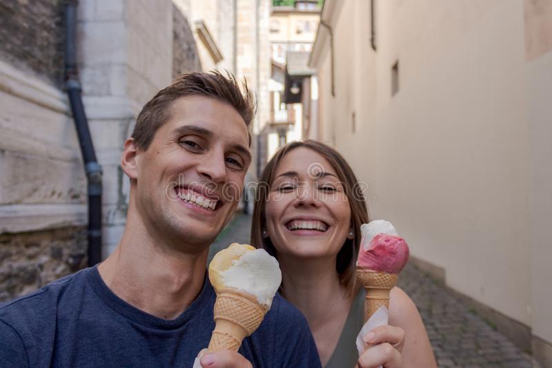 Young couple eating ice cream in an alley royalty free stock images