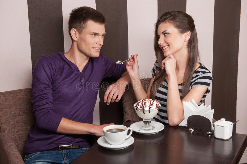 Young couple eating ice-cream in cafe. royalty free stock image