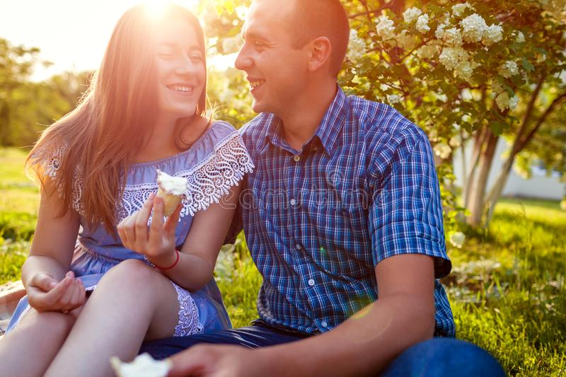 Young couple eating ice-cream and chatting outside. Woman and man chilling out in spring garden at sunset. Lifestyle royalty free stock photo
