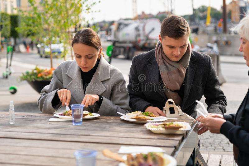 Young couple eating at an outdoor restaurant royalty free stock photos