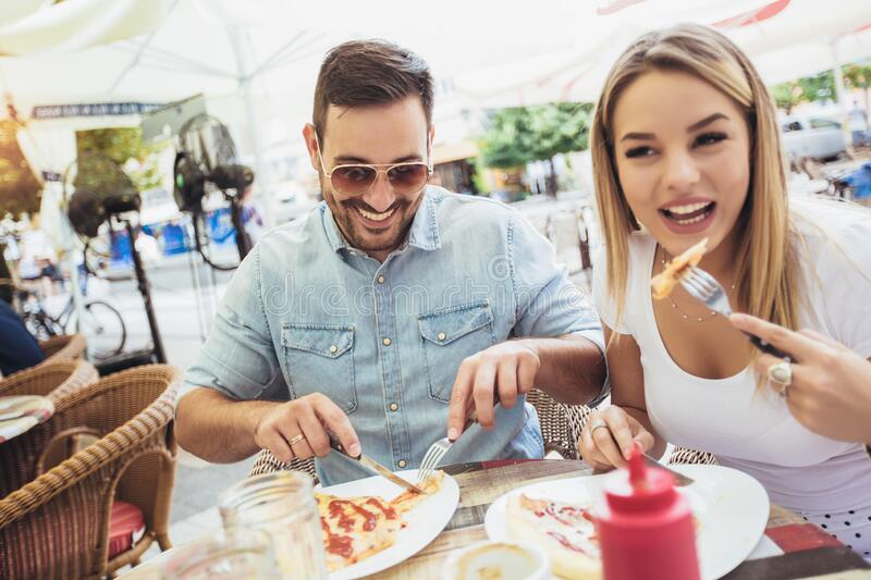 Young couple eating pizza outdoors and smiling.They are sharing pizza in a outdoor cafe stock photos