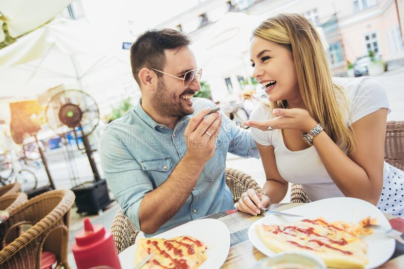 Young couple eating pizza outdoors and smiling.They are sharing pizza in a outdoor cafe royalty free stock image