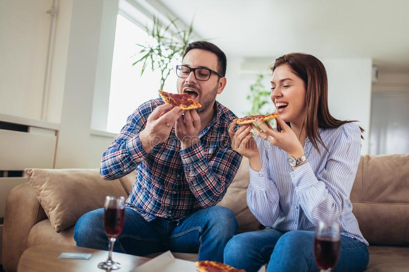 Young couple eating pizza,talking and smiling at home stock photos