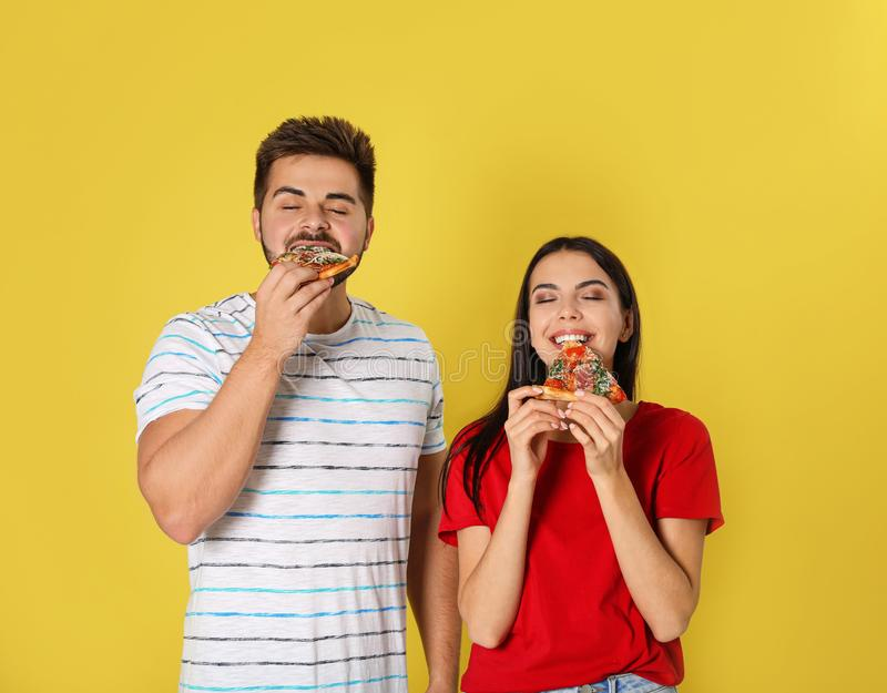 Young couple eating pizza on background royalty free stock image