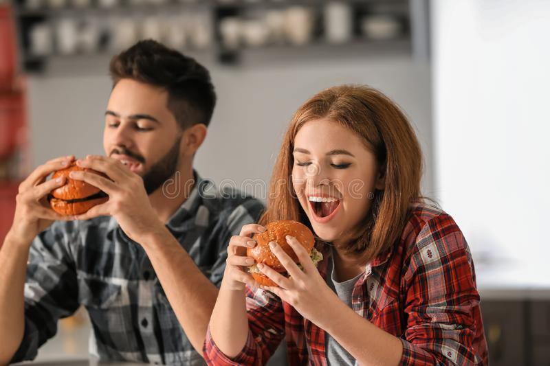 Young couple eating tasty burgers at home royalty free stock photos