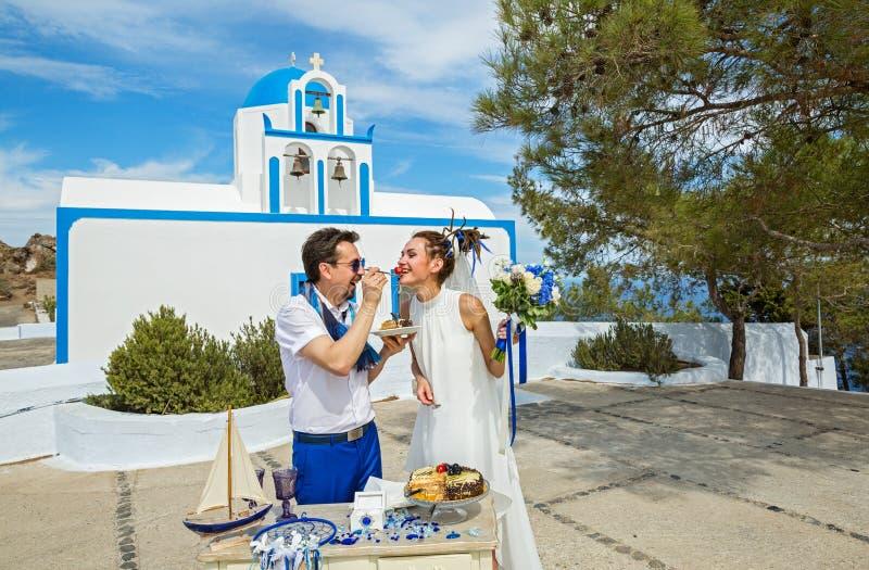 Young couple eating wedding cake stock photography