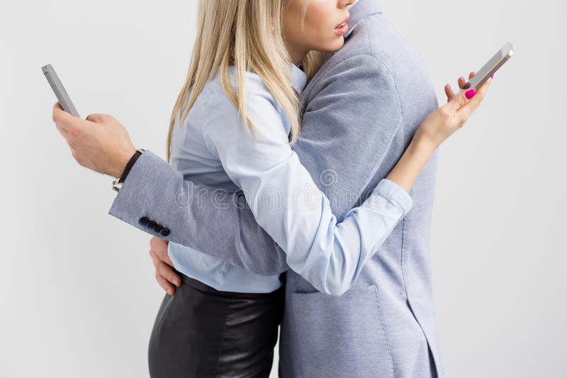 Young couple embrace while keeping busy with their mobile phones royalty free stock image