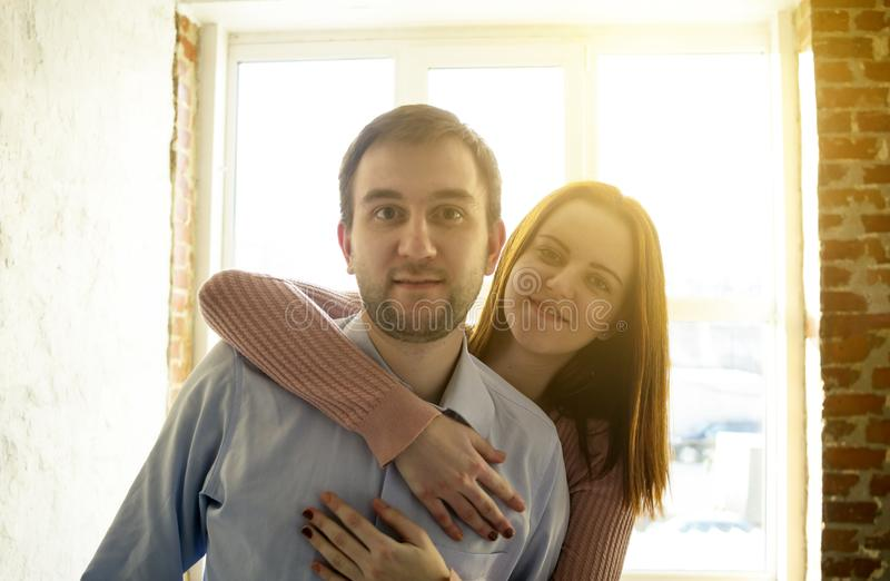 Young Couple Embrace Modern Apartment Big Panoramic Window View, Mix Race Man And Woman Morning Home Interior. Young Couple Embrace Modern Apartment Big royalty free stock photo