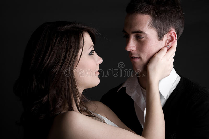 Young Couple Embracing against Dark Background stock photography